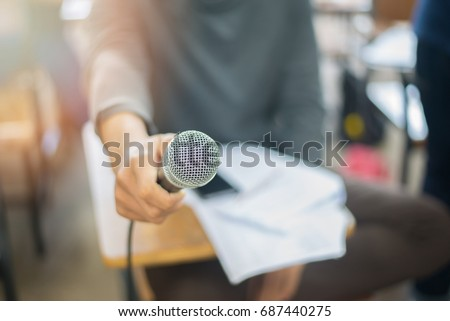 Microphone holds by news reporter, teacher, student, or business person. This microphone image is useful for business magazine, website, books, or any media related to sound system, speaking, singing #687440275