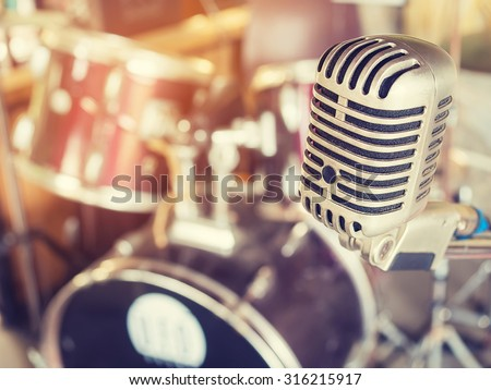 Microphone in a recording studio or concert hall with drum in out of focus background. : Vintage style and filtered process.