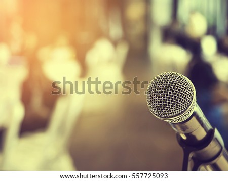 Microphone in business conference room or symposium hall with audience at the meeting room in out of focus blur background. Extremely shallow dof.  Vintage style and filtered process. #557725093