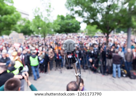 Microphone in focus against blurred protest or public demonstration
