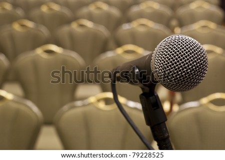 Microphone in front of several rows of empty chairs with shallow depth of field - stock photo