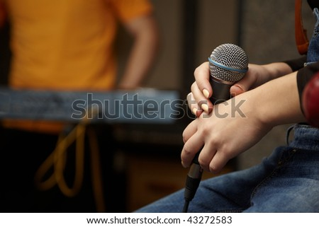 microphone in hand of vocalist girl. keyboard player in out of focus