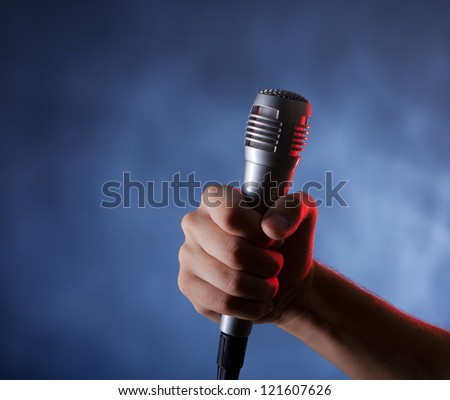 microphone in hand on the dark background