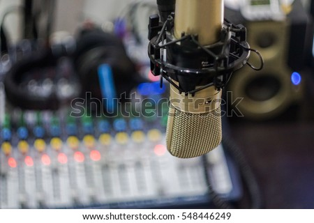 Microphone in radio broastcast room with headphone and monitor speaker