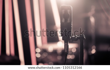 Microphone in recording Studio or concert hall close-up, with drum set on background out of focus. Beautiful blurred background of colored lanterns. Musical concept in vintage style.