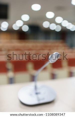 microphone in the foreground. Seminar presentation. Conference room full of empty seats. Red color. Hall for workshops and seminars #1108089347