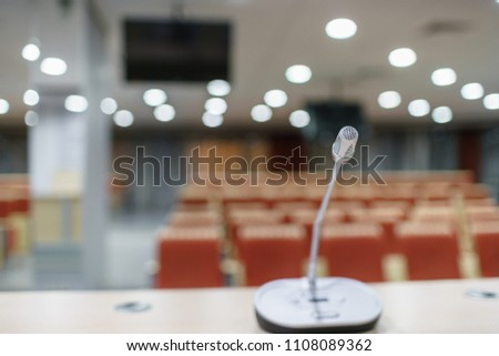 microphone in the foreground. Seminar presentation. Conference room full of empty seats. Red color. Hall for workshops and seminars #1108089362