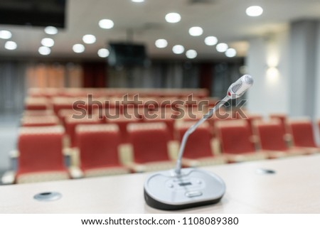 microphone in the foreground. Seminar presentation. Conference room full of empty seats. Red color. Hall for workshops and seminars #1108089380