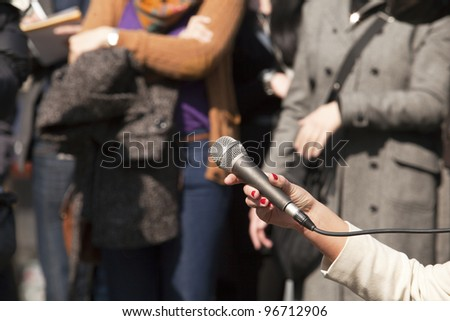 Microphone in woman's hand - stock photo