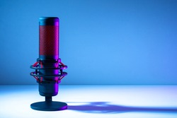 Microphone on a blue background. Space for text. Public speech. Sound amplification. Sound technology. Black and red microphone close-up.