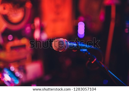 Microphone on a stand ready for live music performance or karaoke night with soft bokeh lights and people silhouettes in the background. Concept for musical singing event, having a good time. #1283057104