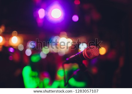 Microphone on a stand ready for live music performance or karaoke night with soft bokeh lights and people silhouettes in the background. Concept for musical singing event, having a good time. #1283057107