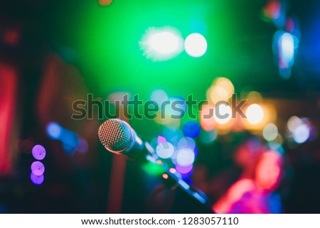 Microphone on a stand ready for live music performance or karaoke night with soft bokeh lights and people silhouettes in the background. Concept for musical singing event, having a good time. #1283057110