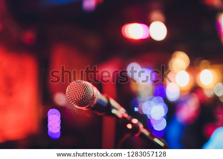 Microphone on a stand ready for live music performance or karaoke night with soft bokeh lights and people silhouettes in the background. Concept for musical singing event, having a good time. #1283057128