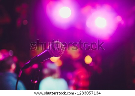 Microphone on a stand ready for live music performance or karaoke night with soft bokeh lights and people silhouettes in the background. Concept for musical singing event, having a good time. #1283057134