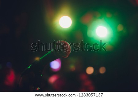 Microphone on a stand ready for live music performance or karaoke night with soft bokeh lights and people silhouettes in the background. Concept for musical singing event, having a good time. #1283057137