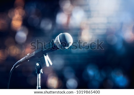 microphone on a stand up comedy stage with colorful bokeh , high contrast image