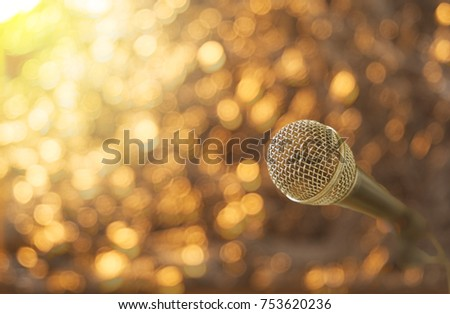 microphone on gold background in flare light blur background #753620236