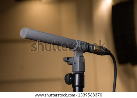 Microphone on the microphone stand in the auditorium, sound events in the audience, the background noise of the audience. #1539568370