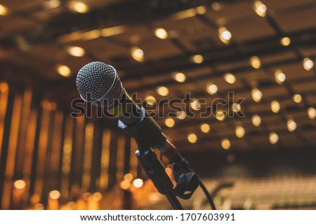 Microphone On The Theater Stage Before The Concert With Empty Seats And Blurred Lights