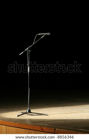 microphone on wooden stage, black background