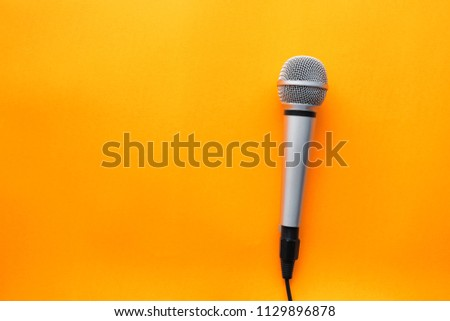 Microphone on yellow background with copy space