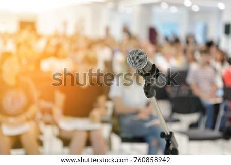 Microphone over abstract blurred of attendee in seminar room