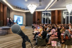 Microphone over the Abstract blurred photo of conference hall or seminar room with attendee background, Business meeting concept