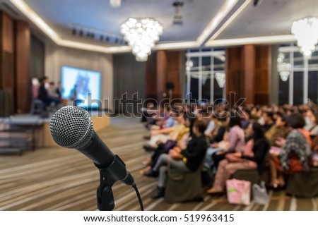 Microphone over the Abstract blurred photo of conference hall or seminar room with attendee background, Business meeting concept #519963415