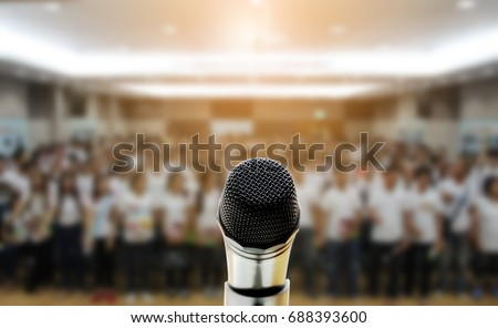 Microphone over the Abstract blurred photo of conference hall or seminar room with attendee background,Small Business training concept