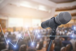 Microphone over the blurred business people forum Meeting Conference Training Learning Coaching Concept with Stock market or forex trading graph.