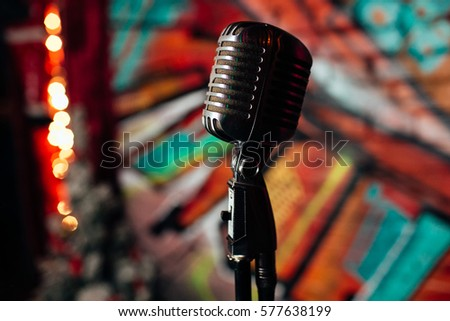 Microphone. Retro microphone. A microphone on stage. A pub. Bar. Restaurant. Classic. Evening. Night show. European restaurant. European bar. American restaurant. American bar. #577638199