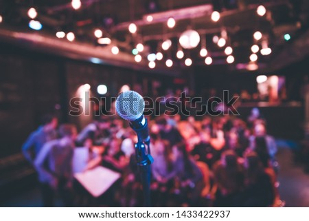 Microphone stand in an event hall, audience in the blurry background