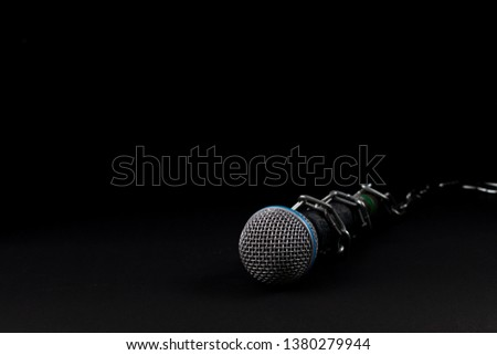 Microphone with a chain, depicting the idea of freedom of the press or freedom of expression on dark background. World press freedom day concept. Using space for advertiser or background.