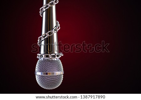 Microphone with a chain, depicting the idea of freedom of the press or freedom of expression on dark background. World press freedom day concept.