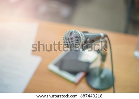 Microphone with blurred background of papers, tablet, and mobile phone on a desk. A microphone can be found in  classroom, business meeting, radio broadcasting station, conference room, or news report #687440218