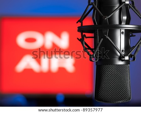 Microphone with blurred on  air sign in the background, for broadcasting,sound related themes