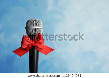 3e089cfc9d3f5 Microphone with bow on color background. Christmas music concept