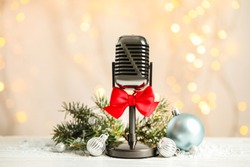 Microphone with red bow and decorations on white table against blurred lights. Christmas music
