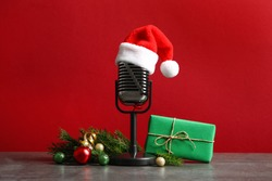 Microphone with Santa hat and decorations on grey table against red background. Christmas music