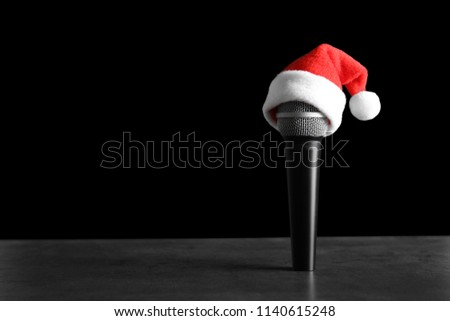 71e04bc0bcbc9 Microphone with Santa hat on table against black background. Christmas  music concept