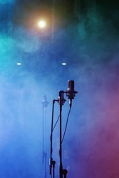 Microphones on smoky stage at concert or music performance background