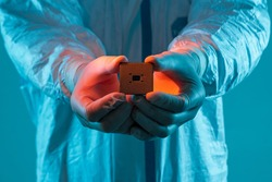Microprocessor in hands in latex gloves in a sterile suit close-up. The concept of ultramodern microchip production, technology, modern plant, chip creation. Selective focus