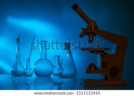 Microscope and chemical utensils on a dark background. Demonstration of chemical experiments to children. Equipment of laboratories. Laboratory research.