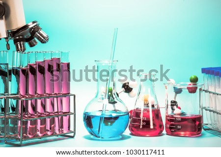 microscope and laboratory test tube on light blue background , science research equipment concept #1030117411