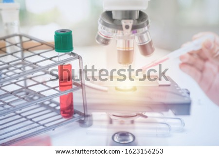 Microscope on the table in laboratory room with laboratory equipment