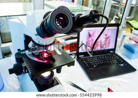 Microscope that was connected with camera at eyepiece into computer, background of laboratory (selective focus)