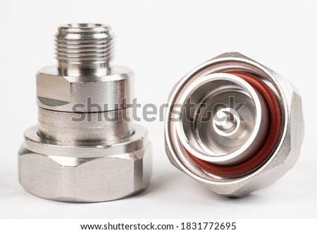 Microwave coaxial adapter 7 16 DIN Male To N Female connector. Concept of radio details. High frequency component with a metallic covering on white background Stock photo ©