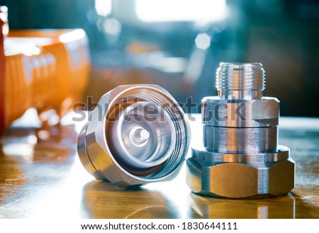 Microwave coaxial adapter 7 16 DIN Male To N Female connector on workshop table. High frequency component with a metallic covering Stock photo ©