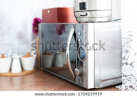 Microwave in the kitchen. The concept of using a microwave to heat and reheat dishes. Silver microwave on the table top.